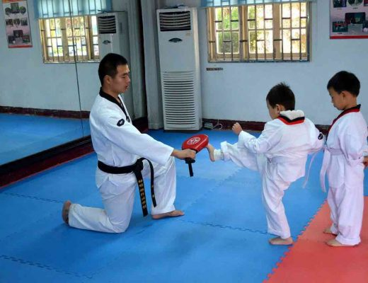 kids in a taekwondo class kicking a pad